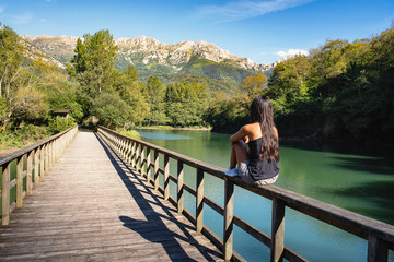 Woman in bridge in Reservoir of Valdemurio, Senda del Oso, Asturias, Spain