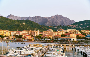 Stunning view of the corsica high mountain range from the harbour of the city Ille Rouse