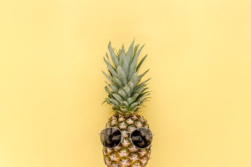 Pineapple in sunglasses on yellow background. Flat lay, top view