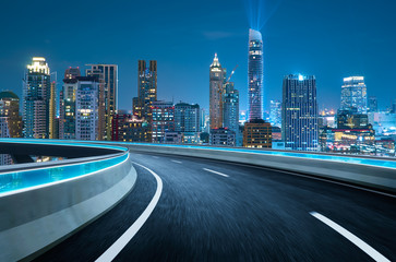 Curvy flyover highway moving forward road with Bangkok cityscape night scene view . motion blur...