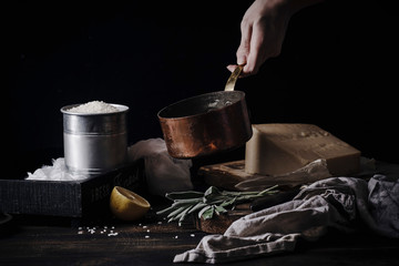 Female hands cooking risotto. Copper pan, rice, parmesan ingredients. Dark background
