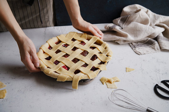 Uncooked berry pie with a lattice decoration on top. Concrete background, cooking process.