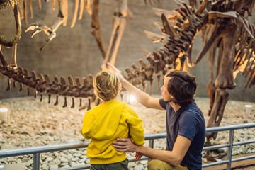 Dad and boy watching dinosaur skeleton in museum Fototapete