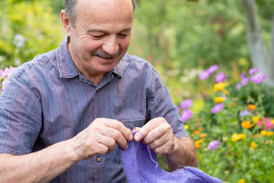 Old handsome man sitting at his summer garden with the knitting needles. A man learn to knit needles sweater. Hobby at senior age