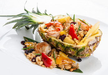Cut pineapple stuffed with rice and Royal shrimps. On white background