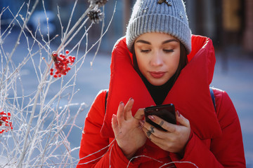 Girl in red winter jacket types something in her phone standing on the winter street.  Christmas, new year and winter holiday concept - Image