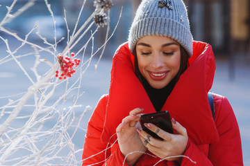 Smilling Girl in red winter jacket types something in her phone standing on the winter street near traditional christmas tree.  Christmas, new year and winter holiday concept - Image