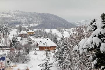 Village with old retro idyllic houses covered with snow in mountain. Village Sirogojno on mountain Zlatibor in Serbia.