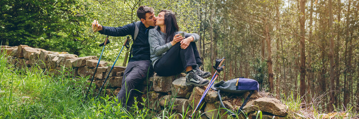 Young couple kissing while making a break to do trekking outdoors