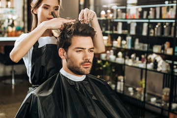 beautiful young hairdresser cutting hair to handsome man in beauty salon
