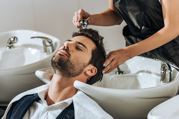 cropped shot of young hairdresser washing hair to handsome client in beauty salon