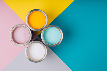 Four open cans of paint on bright symmetry background. Yellow, white, pink, turquoise colors of...
