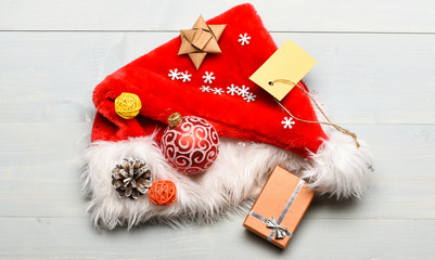 Attributes of winter holidays. New year and christmas decorations. Santa hat with christmas gift box. Christmas presents from santa. Santa hat white background top view. Pay attention to details