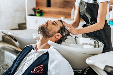 cropped shot of hairstylist washing hair to handsome male client in beauty salon