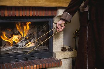 Stoke fireplace. Brass fireplace tongs in hand man