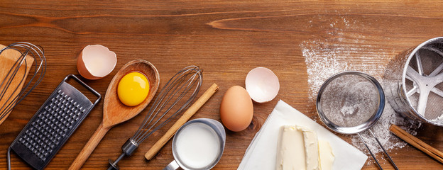 Kitchen, pastry inventory lies on the wooden table. Butter, eggs, wooden spoons, whisk, flour, milk. Top view with copy space, mockup for menu, recipe for culinary classes. Banner