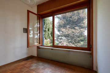 Empty room interior with wooden floor and large open window in country house