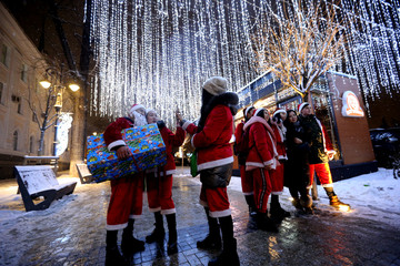 People dressed as Santa Claus pose for pictures next to the Christmas illuminations in Almaty
