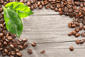 coffee beans and leaves on wooden background
