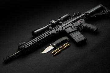 modern automatic rifle with an optical sight lies on a dark background and next to the knife and ammunition