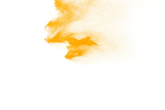 Yellow particles explosion on white background. Freeze motion of yellow dust splash on background.