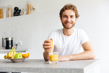 Happy young bearded man at the table at home make a juice with fruits.