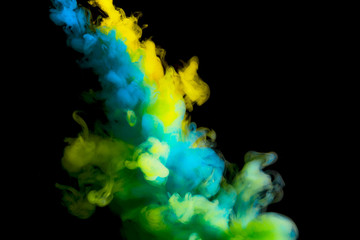 paint stream in water, colored cloud, abstract background, process of mixing multicolored dye on a black background