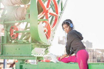 African American Black athletic model wearing pink sports outfit and black hoodie listening to music with blue headphones does a stretch on a green and red construction or industrial machine