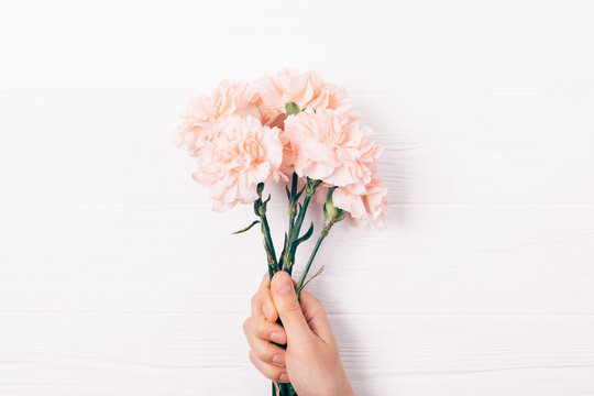 Female's hand holding small pink bouquet