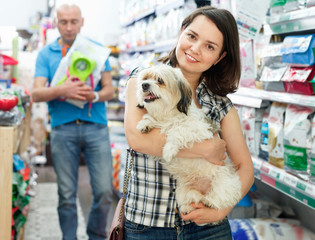 Positive female with dog in pet shop, during shopping with man