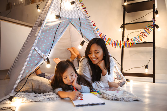 Beautiful young asian woman with her little daughter having fun drawing in album on floor. Christmas concept.