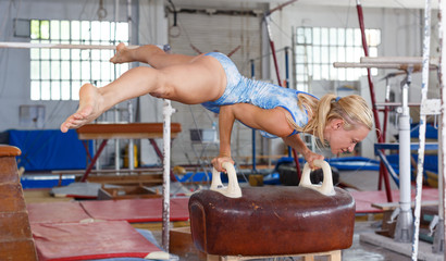 Happy beautiful woman gymnast training action at  vaulting horse