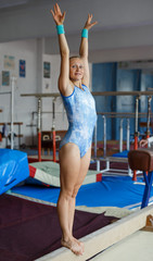 Woman training elements on balance beam