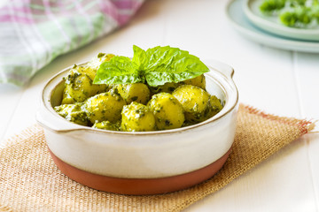 Gnocchi with 'Pesto' sauce, in terracotta bowl, on white wooden background.