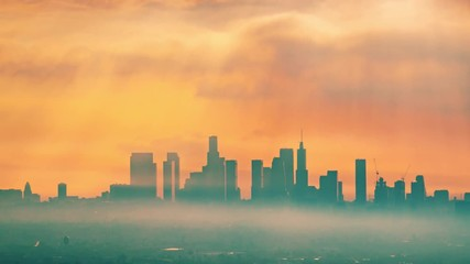 Fototapete - Downtown Los Angeles illuminated by epic rays of morning sunrise sun shining through clouds, zoom out of city skyline. 4K UHD Timelapse.