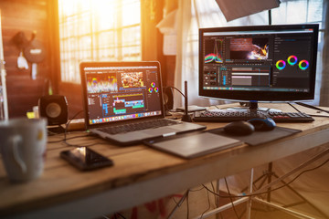 Freelance desktop with laptop computer and monitor review for editor work with content video or...