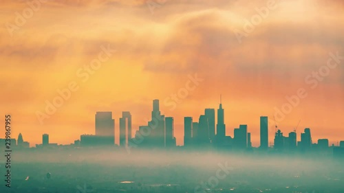 Fotobehang Downtown Los Angeles illuminated by epic rays of morning sunrise sun shining through clouds, zoom out of city skyline. 4K UHD Timelapse.