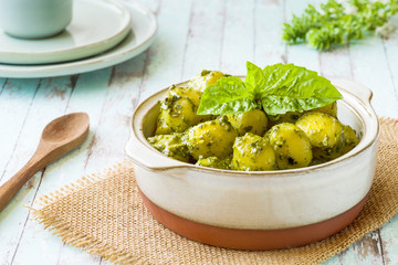 Portion of gnocchi with 'Pesto' sauce, in terracotta bowl.