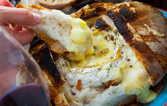 Dish of french cuisine, fresh bread with melted camembert cheese