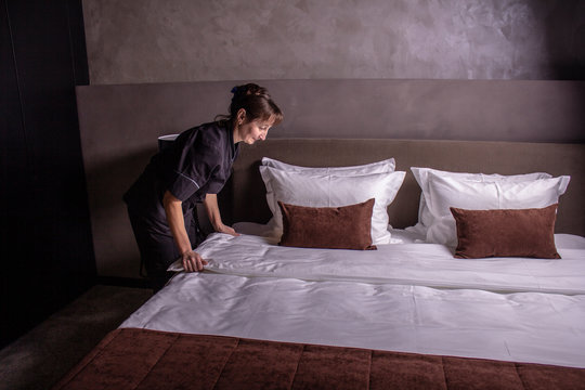 Hotel maid setting up pillow on bed sheet in hotel room