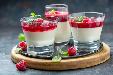 Panna cotta with berry sauce, raspberries and fresh mint.