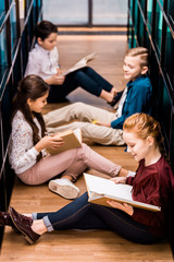 high angle view of four schoolchildren sitting on floor and reading books in library