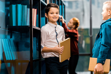 cute smiling schoolchildren holding books while studying in library