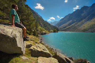 Tourist sitting on the big stone watching a mountain lake Lac de Gaube, Pyrenees Occidentales, France