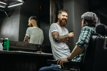 Positive bearded barber looking at his client and smiling