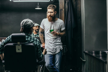 Thoughtful bearded barber looking at his client and holding glass