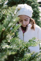 Girl standing near conifer tree on winter day
