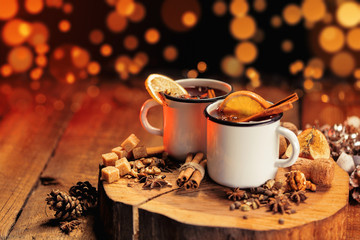 Hot mulled wine in white rustic mugs with spices and citrus fruit on wooden surface. Space for paste text.