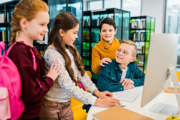 cute smiling schoolchildren using desktop computer together in library