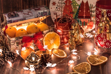 Christmas and new year table, fresh mandarins and dried oranges, stars-garland, decorative red tin with rope, cones and candles